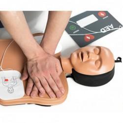 reanimatiepop op de grond met aangesloten elektroden en handen voor borstcompressies